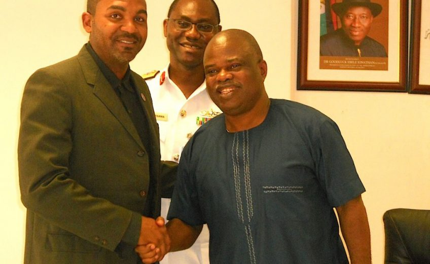 Solomon Ogba in a handshake with Eric Campbell while Commodore Omatseye Nesiama watches / Photo credit: Gongnews.net