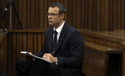 Olympic and Paralympic track star Oscar Pistorius takes notes during court proceedings at the North Gauteng High Court in Pretoria March 13, 2014.