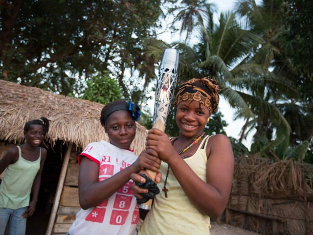 Two smiling girls hold the Queen's Baton in Freetown, Sierra Leone, on Tuesday 31 December 2013 / Glasgow 2014 OC Flickr