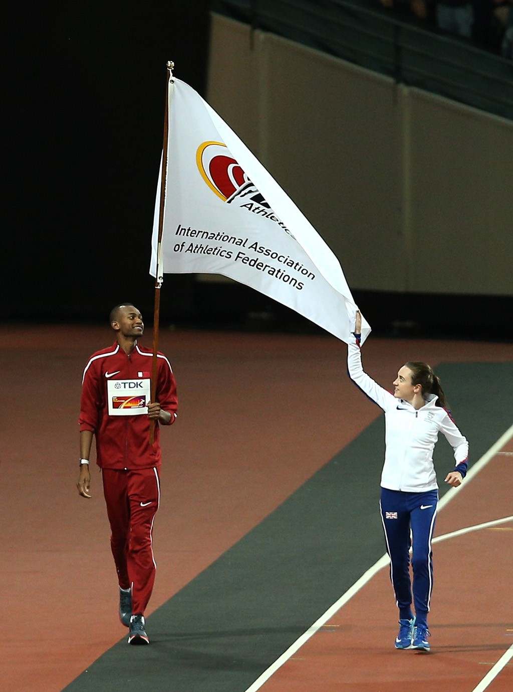 Dr Thani Al Kuwari, President of the QAF, receives IAAF flag from Lord Coe, President IAAF alongside Mutaz Barshim