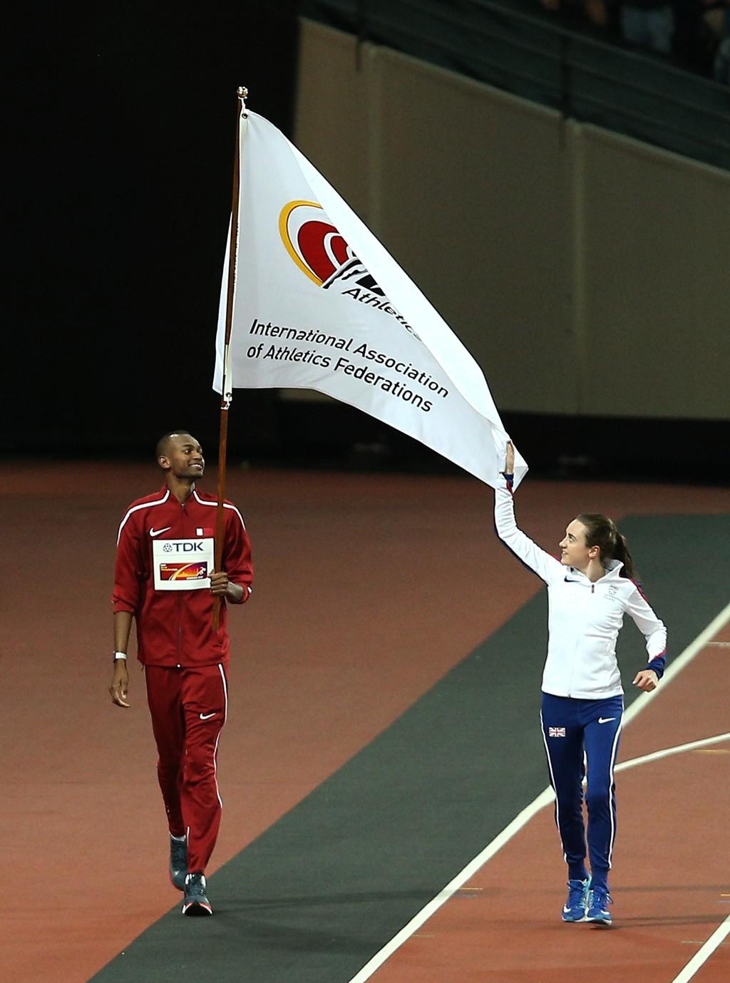 Dr Thani Al Kuwari, President of the QAF, receives IAAF flag from Lord Coe, President IAAF alongside Mutaz Barshim