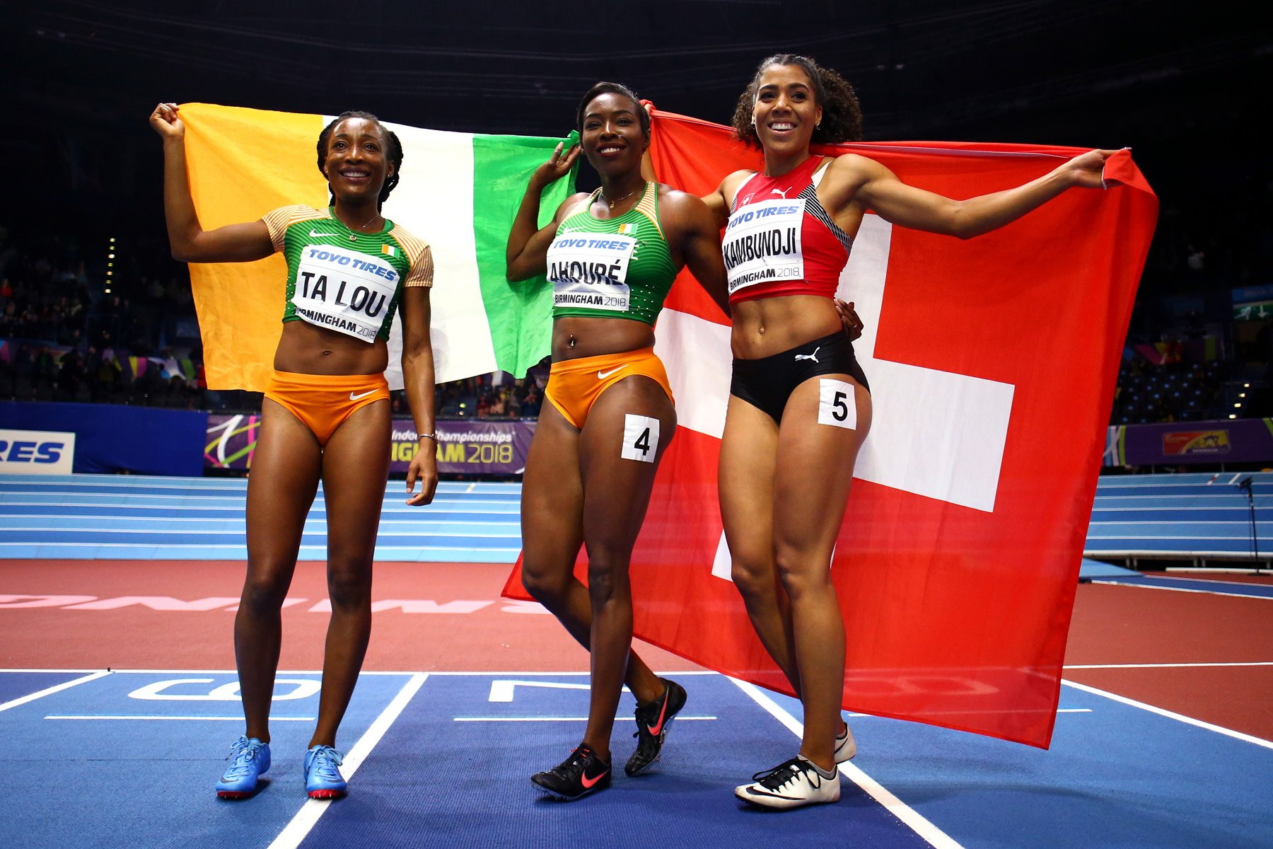 Murielle Ahoure (C) Marie-Josee Ta Lou (L) of Cote D'Ivoire and Mujinga Kambundji of Switzerland celebrates after the 60 Metres Womens Final during the IAAF World Indoor Championships on Day Two at Arena Birmingham on March 2, 2018 in Birmingham, England. Photo by Michael Steele/Getty Images for IAAF