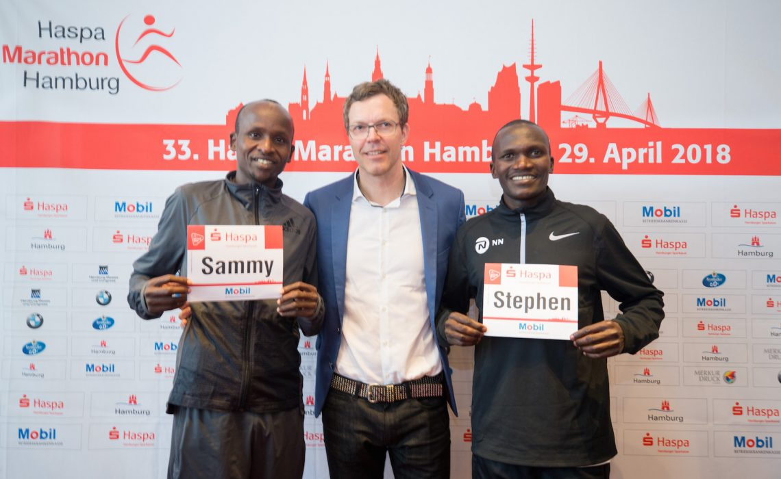Kenyan Sammy Kitwara and Ugandan Stephen Kiprotich together with chief organiser Frank Thaleiser during the press conference in Hamburg. Photo Credit: HochZwei / Haspa Marathon Hamburg