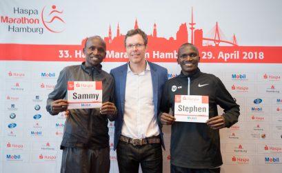 Kenyan Sammy Kitwara and Ugandan Stephen Kiprotich together with chief organiser Frank Thaleiser during the press conference in Hamburg. Photo Credit: HochZwei / Haspa Marathon Hamburg