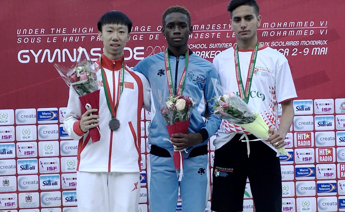 Botswana's Bernard Olesite (C) with Sheng Luo of China and Mehdi Sefrani of Morocco on the podium after the Boys 400m medal presentation at Gymnasiade 2018 in Marrakech / Photo Credit: Yomi Omogbeja