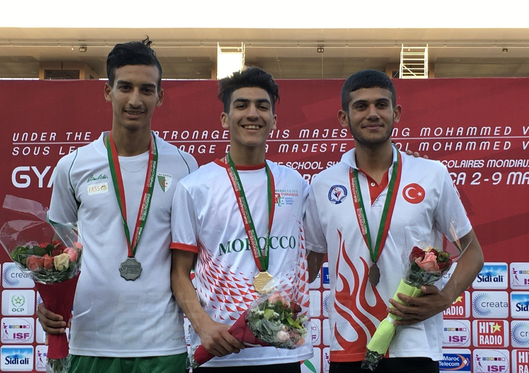 Fouad Messoudi (MAR) Hamdani Benahmed (TUN) and Tarik Demir (TUR) on the podium for Boys 1500m presentation at the Gymnasiade 2018 in Marrakech / Photo Credit: Yomi Omogbeja